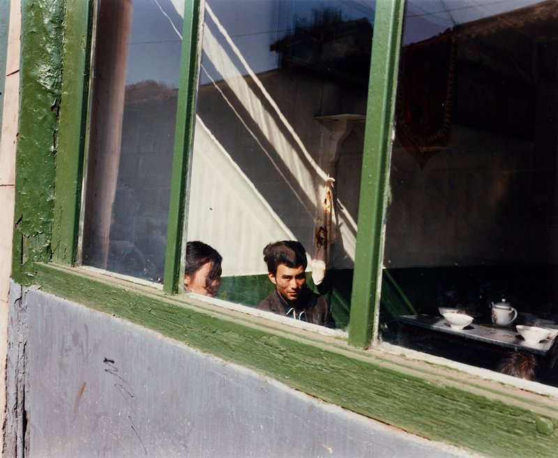 man and woman seen through a window with a green-painted frame; woman has a lock of hair over her face; bowls and teapot on table at right