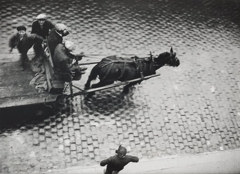 view from above of four figures riding on a cart pulled by a horse, on a brick street; figure on sidewalk at bottom center