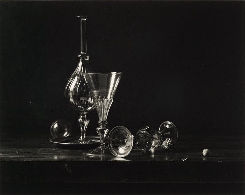 glass decanter on tray; three fancy wine goblets--two fallen over and broken; glass ball behind tray at left; small ball (?) on table, LRC