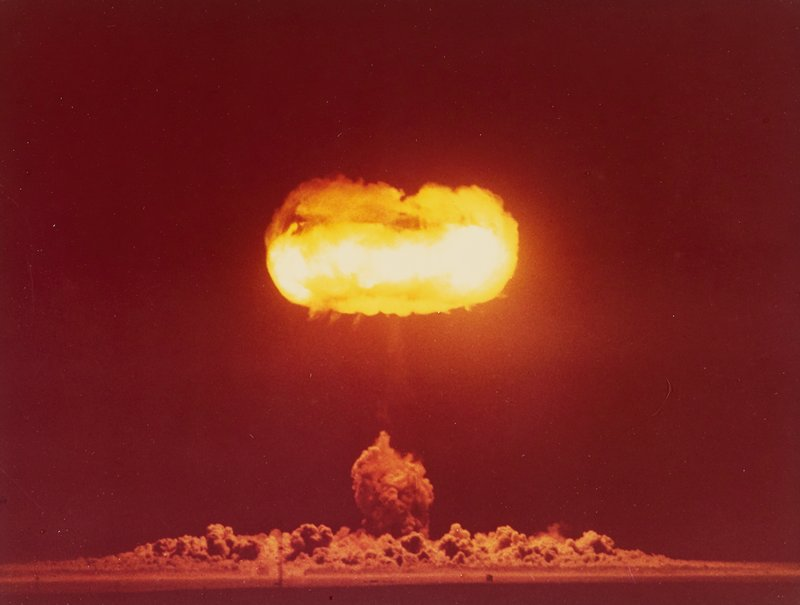 fiery atomic bomb mushroom cloud; dark orange sky; flaming lozenge-shaped with dark dust clouds on ground