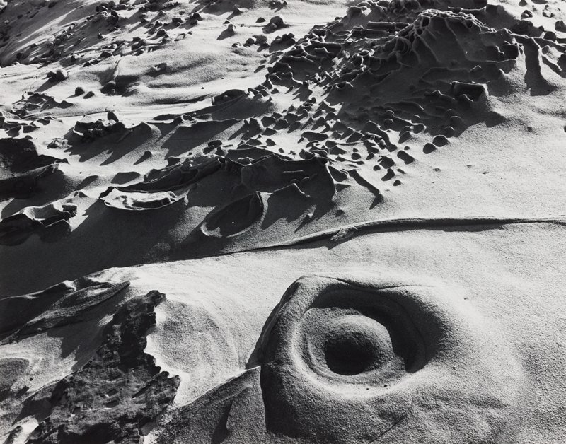 abstract image; round forms in sand; some vertical elements in clusters at top half of sheet