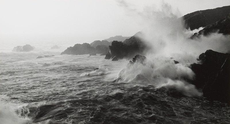 waves crashing on rocky shoreline at left