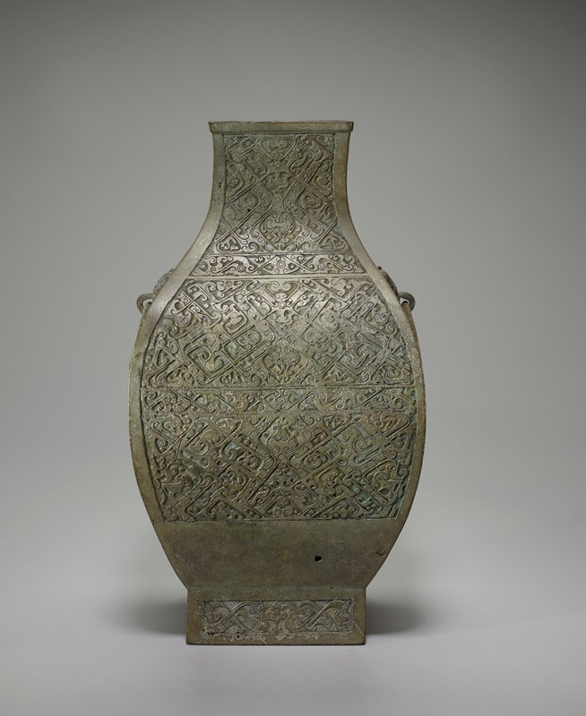 This vessel has the beautiful proportions and soft profile typical of the group of Hu once inlaid with turquoise, other semi-precious stones, or perhaps niello. The animals which inspired the decor have been so corrupted and dissolved that the whole surface is a maze of lines, hooks, and spirals. Remnants of interlaced dragons are still discernible in the narrower bands, and occasionally, in the highly geometricized decor, a definite shape, such as the dragons flanking the central medallion, may be isolated. These medallion-like figures appear in the median line, with the decor pattern symmetrically arranged on each side. The middle one of the figures- best seen in the neck belt- is a t'ao-t'ieh mask with forehead shield, horns, and nostrils as seen in many appliques. The T'ao-t'ieh on the handle ring displays an interesting revival of a Yin-time motif a figure between the eyes showing one round knob in the center surrounded by six other knobs. Patina silvery green.