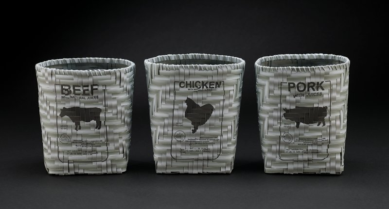 """woven basket with square bottom made of strips of grey paper; strips printed on front of basket with a label reading """"BEEF WITH NATURAL JUICES"""" and other text and silhouette of a cow"""