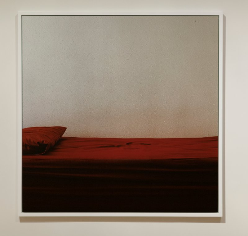 [MP-JONES-00206]: color photograph; lower 1/3 is a red couch with pillow on L side and top 2/3 is a white wall