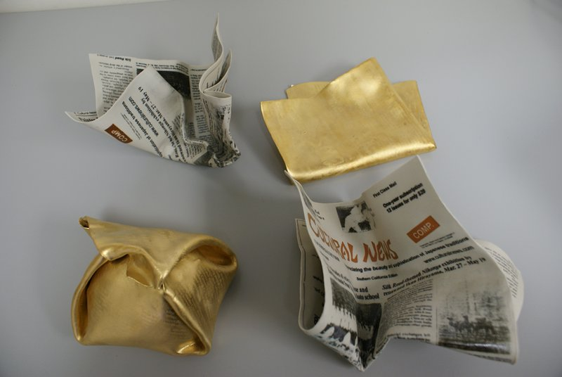 "four pieces: realistic ceramic newspaper pages all the same front page of ""Cultural News""; two of the pieces are coated in gold; one of the gold pieces is somewhat folded, while the other is bundled up like a parcel; other two pieces are realistically crumpled"