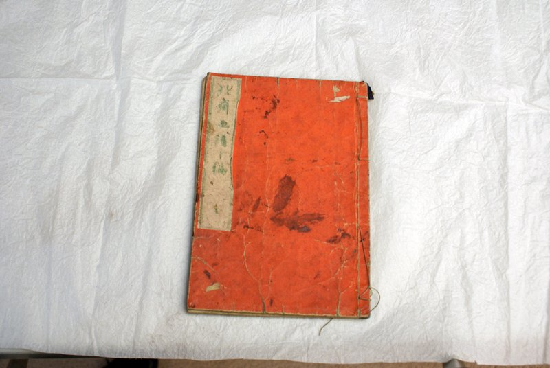 color woodblock printed book with red cover; various images of people, landscapes, birds, etc.