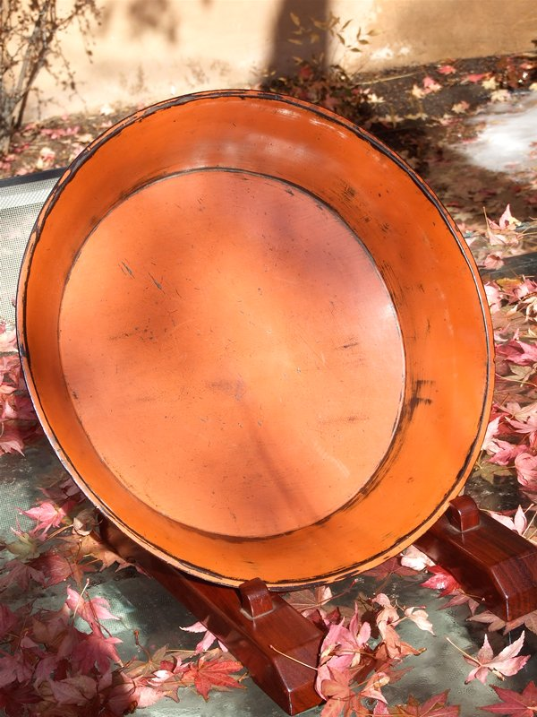 red elevated bowl with three carved short black legs