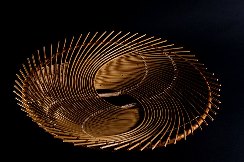 round form with reeds in fanned, spiraled pattern spilling over the edges