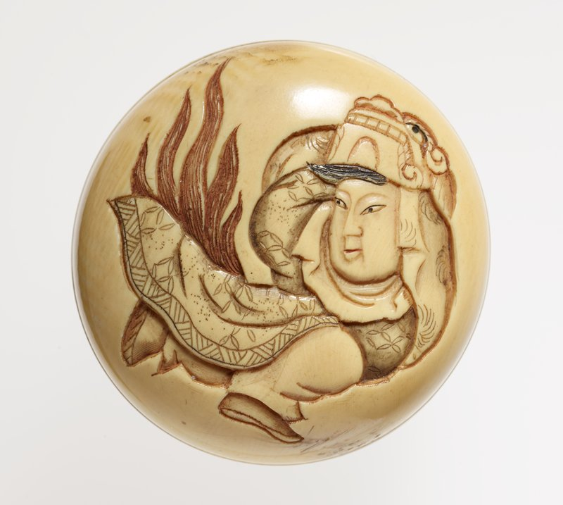 round ivory netsuke with carved image of male figure looking to L with dragon on head; flames at L; incised drum on back