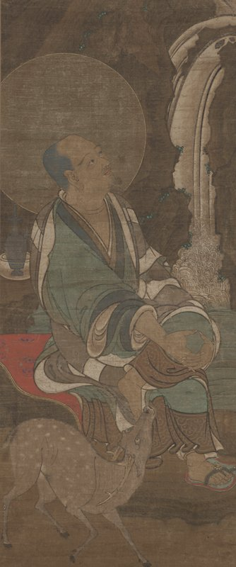 man seated with crossed knee, hands on knee, looking at waterfall on R; wearing green kimono with blue and white accents; halo around his head; deer in foreground looking up at man
