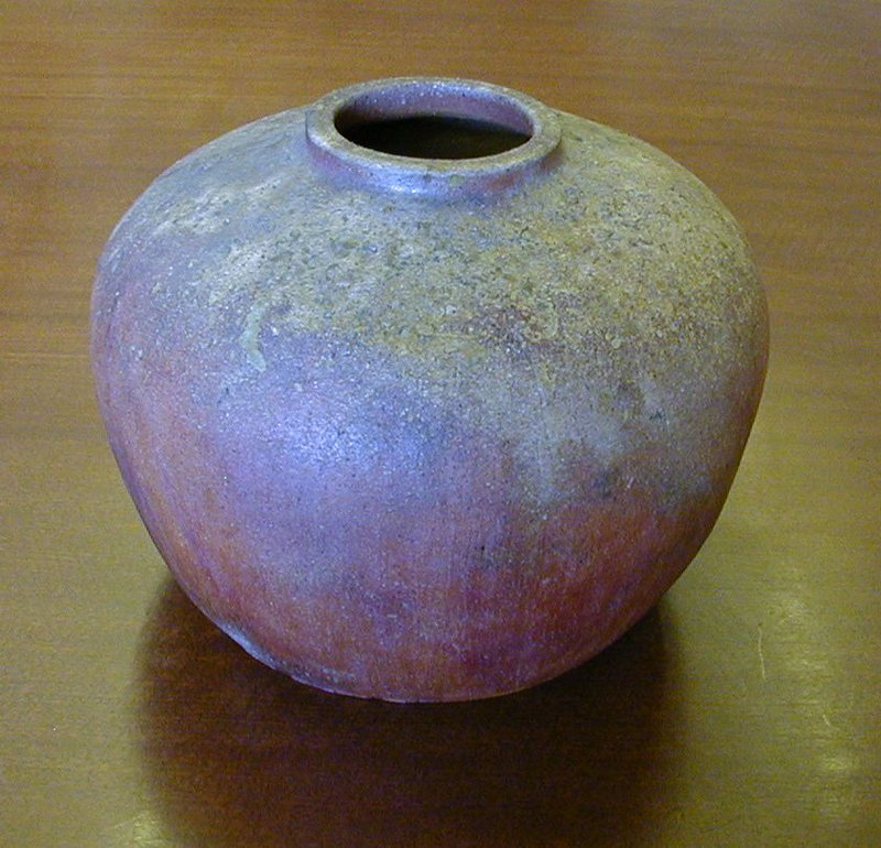 squat, slightly irregular rust colored vase with spotty patches of gray, brown, and dark green glaze around top; markings resemble lichen with some included organic matter in glaze at top; natural markings on side