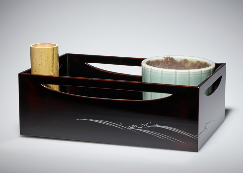black lacquered, high walled tray with crescent-shaped cutouts on sides near top; simple, silver wavelike pattern painted on each side; celadon glazed cup with vertical incised lines and incised square motif around lip; small bamboo cylinder