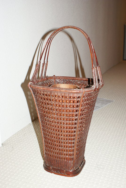 tall, 4-sided basket; flares outward at top, forming wide mouth; 4-pronged handle, woven together at upper center; crisscrossing weave pattern; mountain pattern incised around bottom lip; bamboo inner cylinder