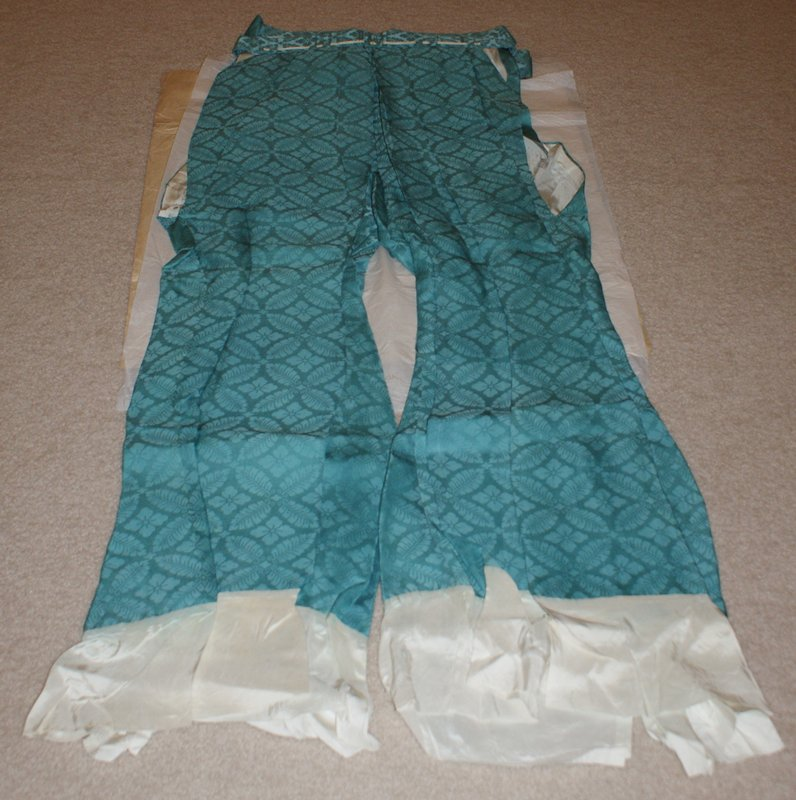 long turquoise pants with white cuffs; sash at waist