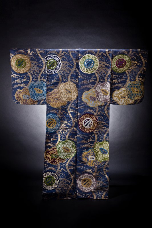 dark blue background with golden wavelike motif; embroidered sword guard designs in multiple colors