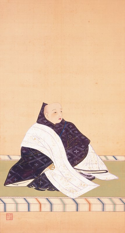 3/4 view of monk in purple and white robes facing PL; monk is seated on green mat with white, blue, green, and orange striped border; monk holds golden object in PR hand