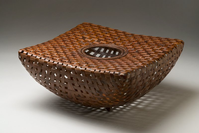 flat, square topped basket with round opening; sides gracefully bow downward onto a narrower foot; generally triangular shaped; open weave of wider bands of five thin bamboo strips each; black lacquered bamboo water container