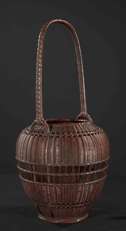 bulbous, closely woven flower basket; center decorative band of open weaving in grid like pattern; bottom and top bands of open weave in crisscross pattern; tall handle with square-patterned weave that ends in two-pronged forks in basket interior; center lacquered bamboo cylinder