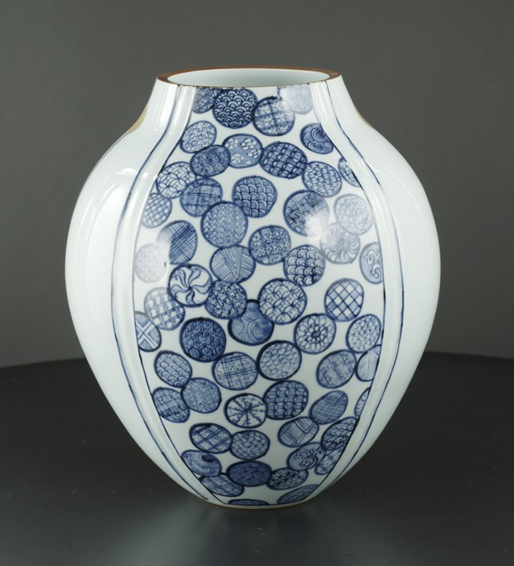 rounded, white, bud-shaped vessel with two panels of blue circles filled with patterns; vertical blue lines dividing panels; two gold spots near top; brown lip
