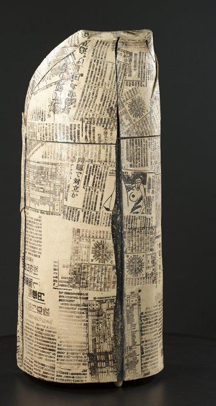 irregular columnar form with newspaper pattern; vertical split up front and back; several inherent jagged seams and cracks