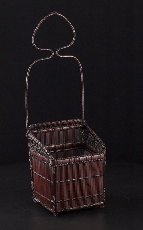 open weave basket with decorative knots and braiding at joints; tall handle mounted at back with bottle-shaped design; looping, open weave pattern at top on L and R sides; inner bamboo cylinder with lattice top