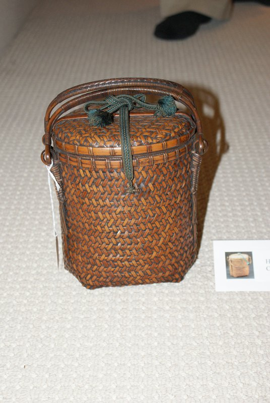 oval tea basket with lid; closed chevron weave; two handles; green cord at top; blue brocade lining inside; two green tassels