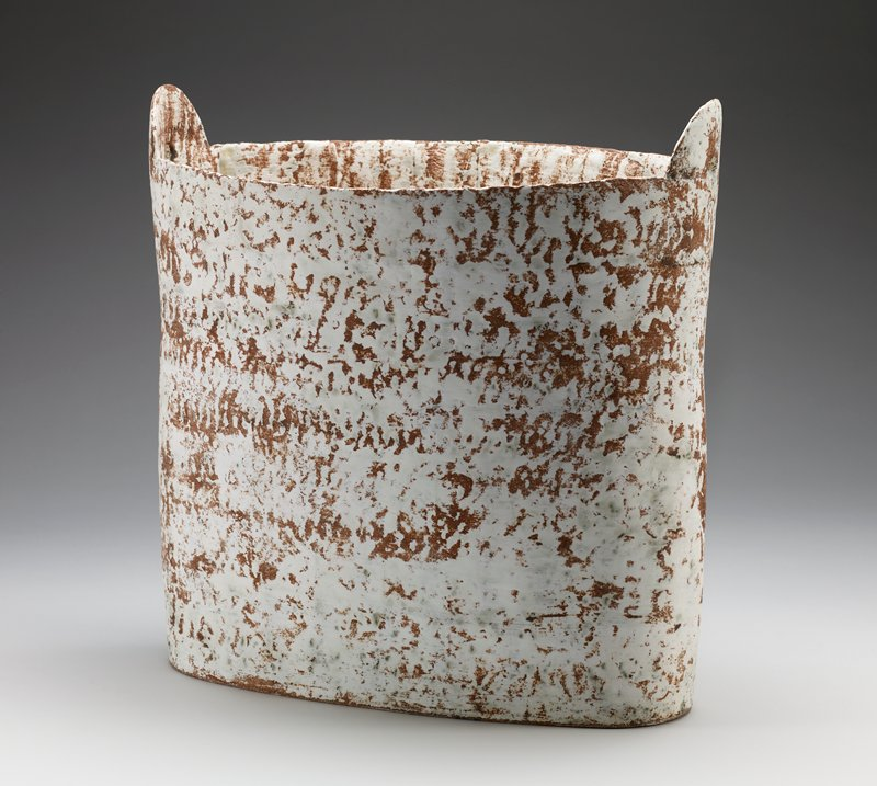 tall, oblong stoneware vessel; stoneware tab with hole on either end at top; slightly flared at top; white and grey glaze with brown and rust colored accents