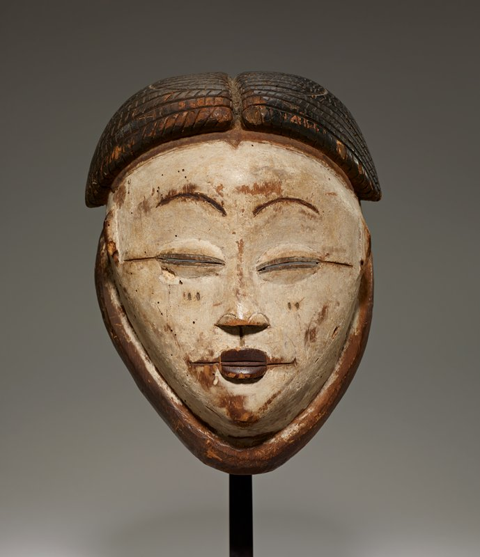 small face mask with white skin; coffee-bean eyes with slit openings; coffee-bean shaped lips with wider line for mouth; rather flat nose; arched thin eyebrows; very small, high ears; hair in cornrows above the ears; scarifications (?) on cheeks and outer sides of eyes