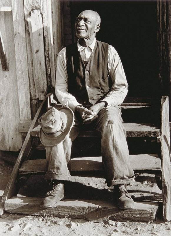 balding negro man sitting on steps with battered hat on proper right knee; wearing vest with white shirt; hands folded in lap.