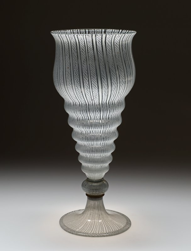 "very tall tulip-shaped bowl with a tapering hollow base formed into six graduated knops or steps, on a cushioned knop between collars and a spreading foot folded at the rim, entirely decorated in ""vetro a retorti"" with a striped pattern of flattened gauzes and ribbons; clear glass with white decorations"