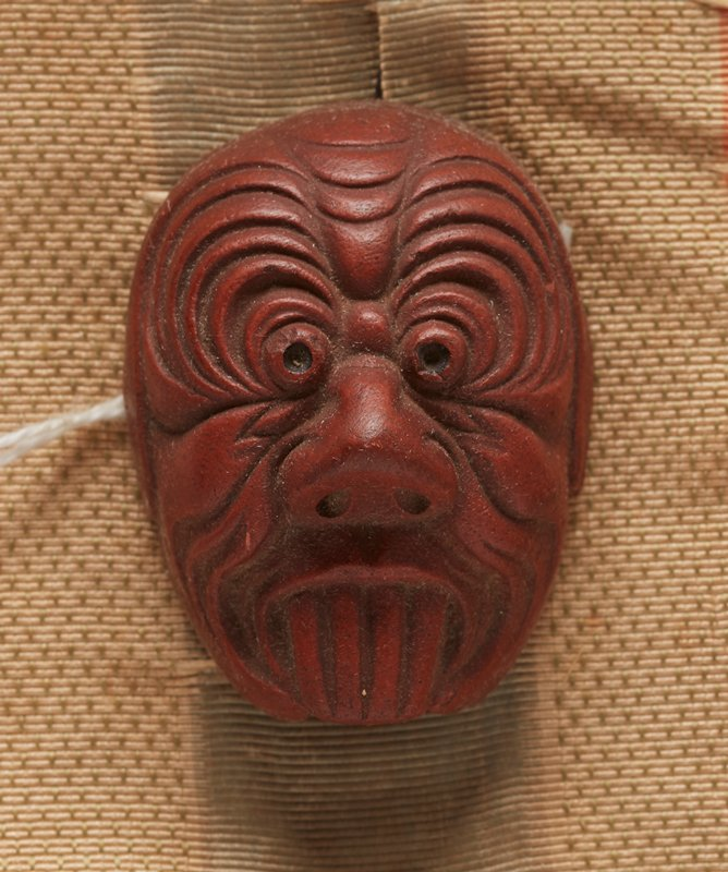 netsuke in the form of a mask; red clay; demon face with long top fang-like teeth; open mouth without bottom jaw; long pointed nose; beady eyes with radiating wrinkles; wrinkles around mouth and nose; 2013.29.1217.1-6 received attached to patterned orange, cream and blue ribbon (ribbon in poor condition--shredded)