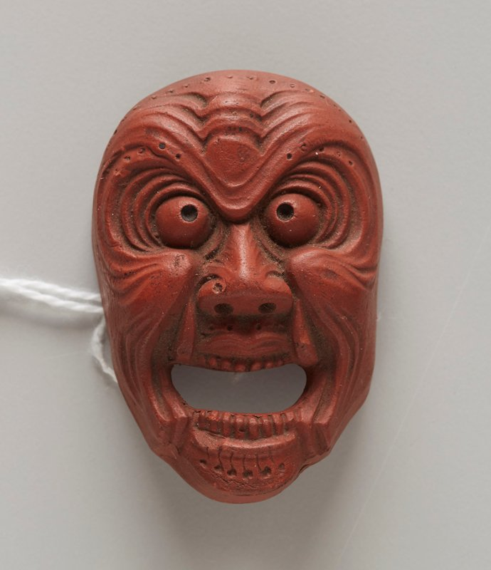 netsuke in the form of a mask; red clay; demon face with open mouth with teeth showing; round beady eyes; high cheekbones; radiating wrinkles/lines around eyes and mouth and on forehead; vertical lines with dots on chin