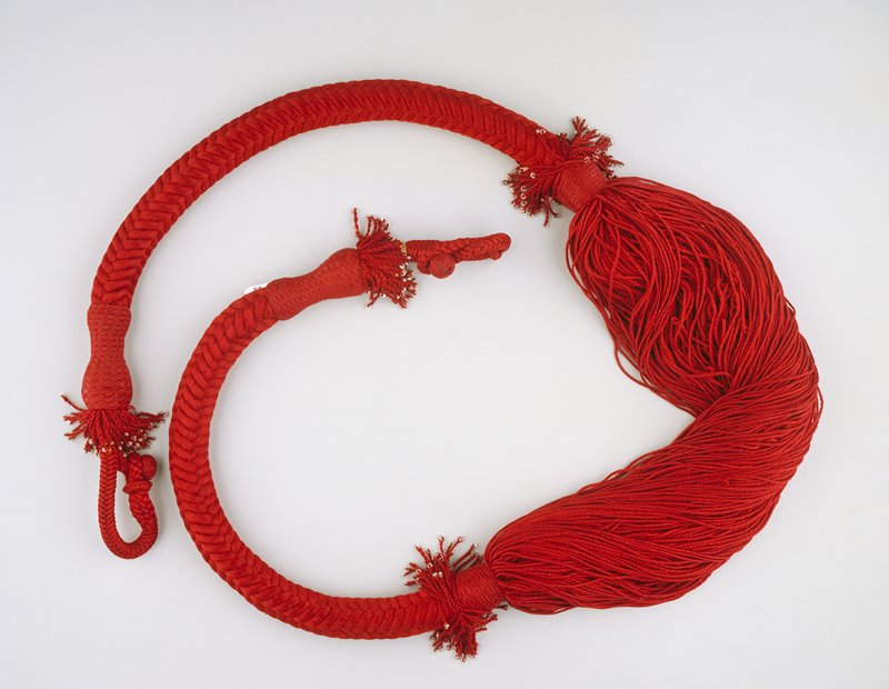 loop with button closure on each end with short fringe of twisted cords with clear and white beads followed by stiff twisted and braided sections, fringe and beads and loose rows of twisted cords at center; maroon thread