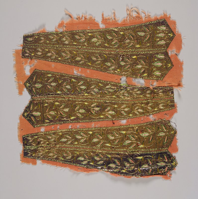 3 pairs of necktie shaped embroidery on salmon pink fabric; gold metallic ground with green and yellow scrolling vines with red and white striped 'pods'