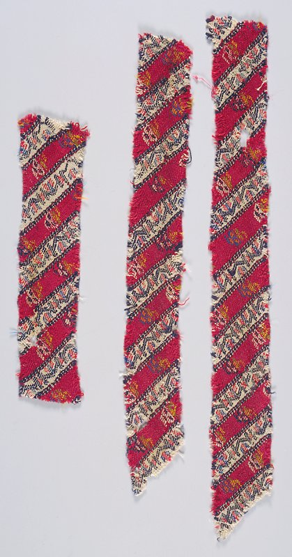 3 separate textile fragments cut on the diagonal from UL to LR; vertical bands of alternating white and maroon; geometric designs in black, red and blue on white band; floral sprays in white, blue, yellow, green and orange on maroon bands. Woven fabric