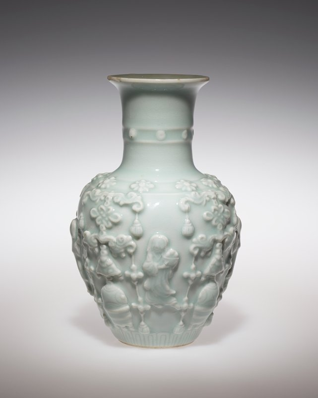 celadon green glaze; small ring foot; rounded form tapering to long neck with central rib; wide, outward-flaring mouth