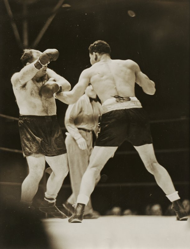 two boxers in the ring, with dark-haired boxer at right seen from back with feet wide apart; balding boxer with dark chest hair at left, holding his PL arm in front of his chest and his PR gloved hand in front of his face; man wearing slacks, shirt and bowtie in middle ground visible between two boxers