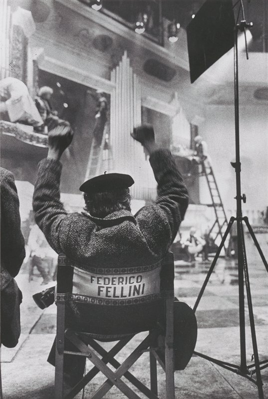 "man, seen from back, seated in a director's chair with ""FEDERICO FELLINI"" on the backrest, wearing a tweed coat and a black beret, with arms up; stage (?) with figures in background"