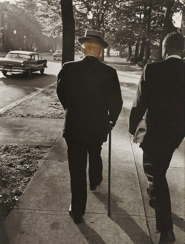 two men, seen from back, walking down tree-lined sidewalk with cars on road at left; man at left wears a small-brimmed fedora and walks with a cane; man at right carries a newspaper; both men wear dark suits