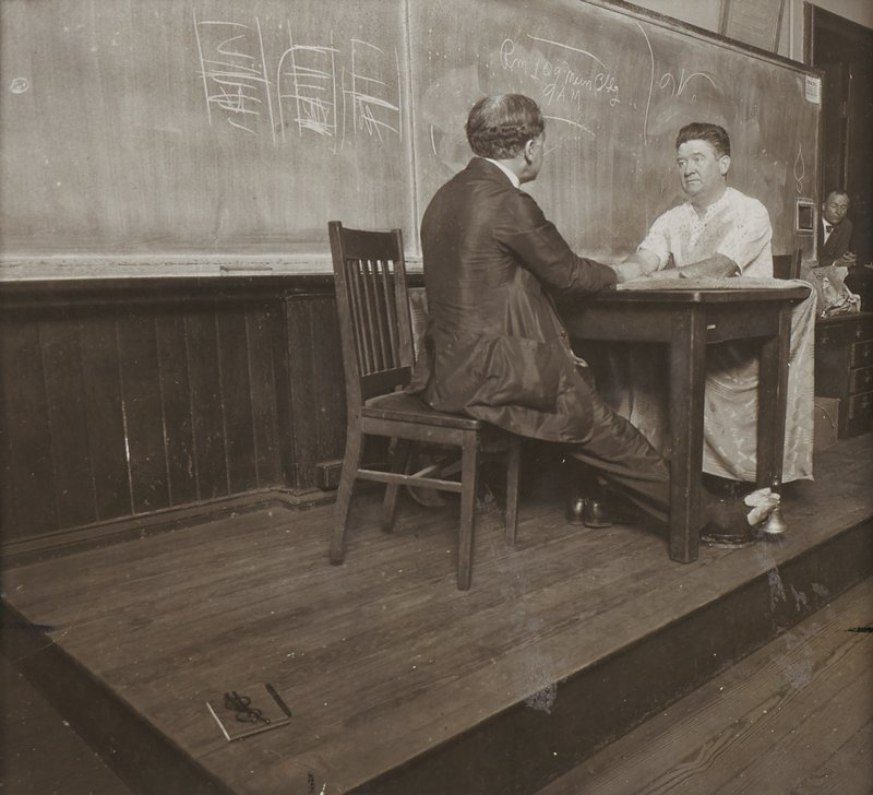 man with curly hair wearing a suit, seen 3/4 from PR, seated on a side chair with his legs outstretched under a table, holding a bell with his bare toes; another man at opposite side of table wearing a light-colored short-sleeved shirt; chalkboard behind men; book with eyeglasses on top, LLQ