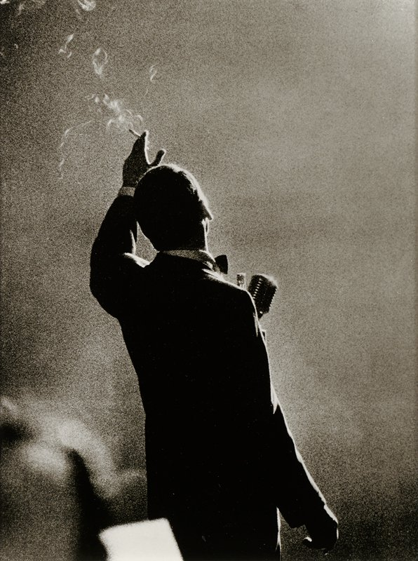 torso and head of man seen from back wearing a tuxedo, standing in front of a microphone and holding a cigarette in his PL hand, which is held up