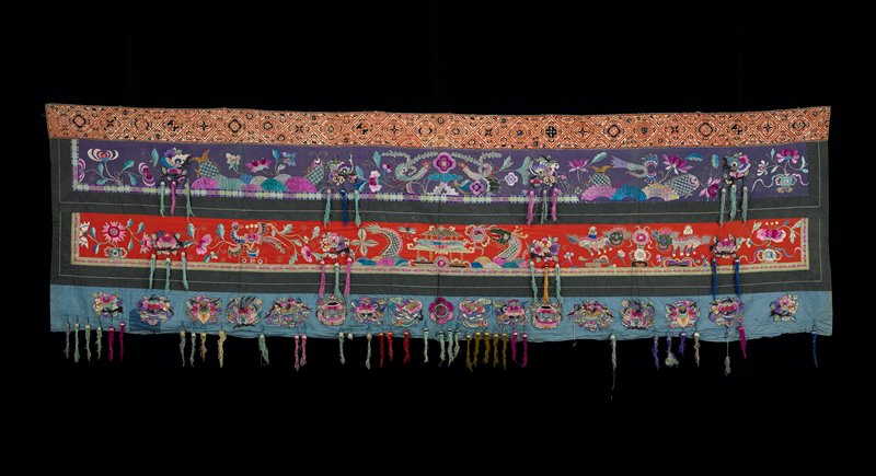 four distinct bands; top band embroidered brown and black diamond and floral patterns; two central bands of embroidered floral designs, with fish on top and dragons below, on purple and red fields; lower band applique floral groups; tassels attached throughout