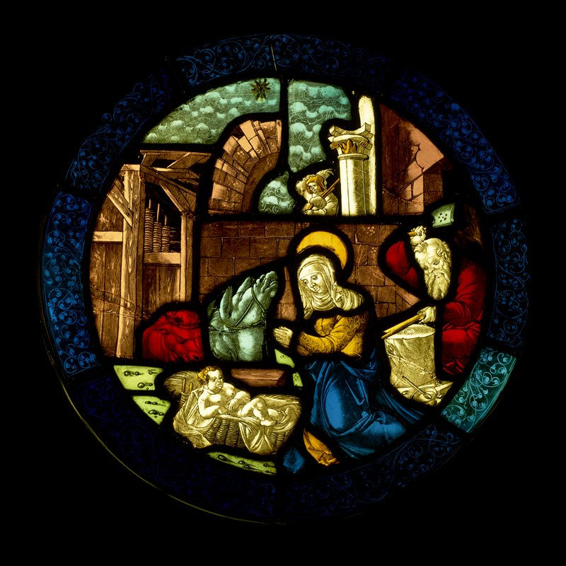 round stained glass panel depicting the Nativity, with baby Jesus in a basket at bottom center, kneeling Mary praying before Jesus, Joseph hammering at one side, and horse and cow behind baby Jesus; angel at top center; scrolling border