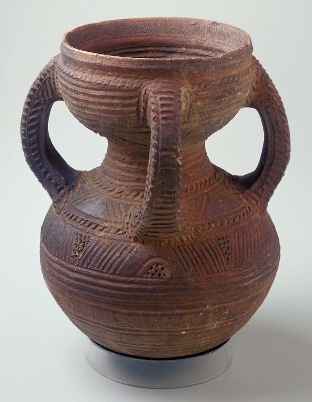 four handles; rounded lower body tapers at center and flares out at top; incised decorations