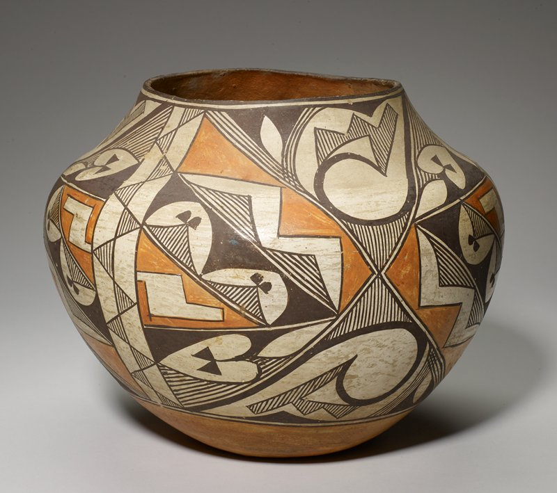 concave underside; outward-flaring sides to rounded small shoulder; wide mouth rim on short, wide neck; decorated in brown, cream and orange with geometric designs with zigzags, triangles, parallel lines and arcing forms