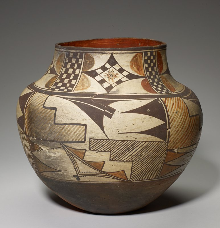 concave underside; outward-flaring sides to small narrow shoulder with short wide neck; rust red inner rim and band at bottom of body; cream-colored band around neck and body decorated with dark brown and rust geometric designs including zigzags, parallel lines; rust half-circles, diamonds and checkerboards