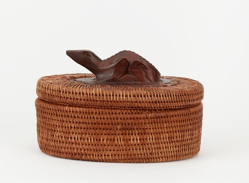 ovoid container with cover; medium brown coiled plant fibers with ovoid wooden disc on bottom and ovoid wooden element on cover, carved with a three-dimensional baby crocodile (?)