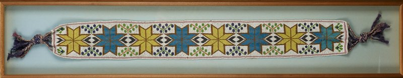 """beaded sash with grey, tan and purple braided and knotted fringe at each end; white ground with alternating blue and yellow eight-pointed stars separated by stylized stems with round """"flowers/leaves"""" in either brown and green or green and purple; amber-colored beads border each star; pink rectangular border over entire design; received framed"""