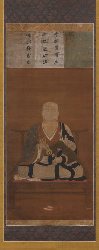 male figure seated on raised chair with shoes on ground; holds metal object in PR hand and an open black object in PL; spotted white robe with black grid pattern, and green sashes; figure is bald and has large earlobes